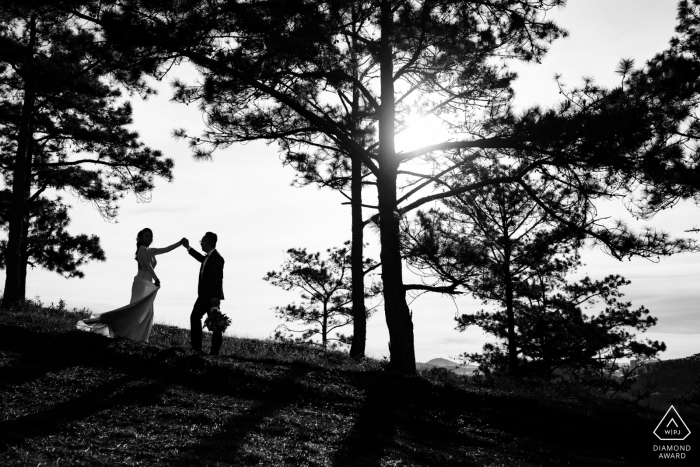 Dalat engaged couple are Dancing together at sunrise under the big trees