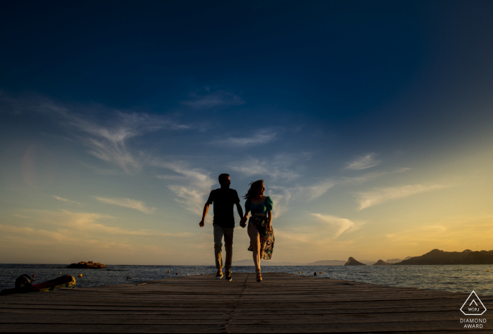 A couple is Playing on the jetty during their sunset Aguilas - Spain engagement photo shooting session