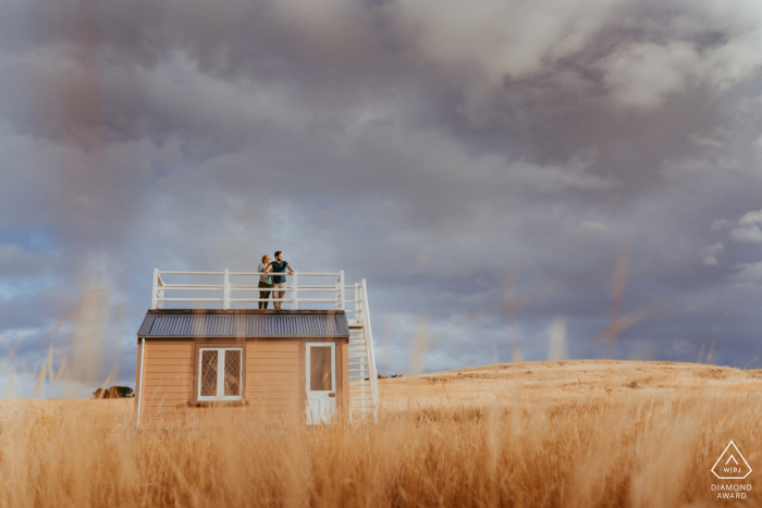 Godley Head Couple standing on roof of old antarctic hut during their Christchurch NZ engagement photo shoot