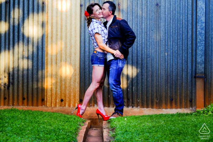 A vibrant, warm and colourful couple against an industrial, cold and grey backdrop, playing on contrasts at the Prince Charles Airport, Harare, Zimbabwe