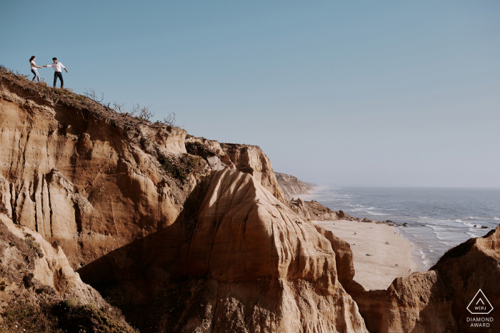 a Portugal Bride and groom playing on the top of a hillside overlooking a beautiful beach in Vale Furado, Nazaré