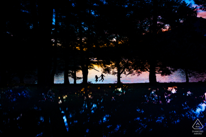 Da Lat evening photo shoot of a couple silhouetted and jumping at a beach with tall trees