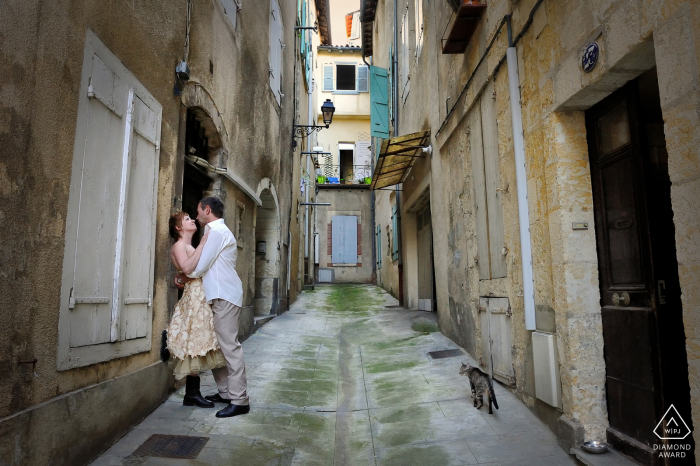 A hugging couple in the little street of Auch. A cat walking is looking at them