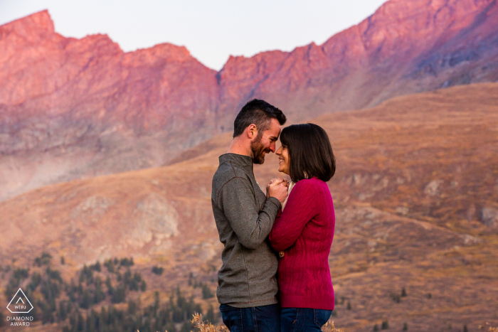 The warm glow on the distant mountains contrasted the freezing temperatures on top of the pass, so the couple cuddled up close to keep warm at Guanella Pass, Georgetown, Colorado, USA