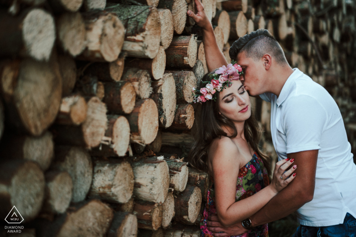 Pobłocie Wielkie Couple together against a wall of cut and stacked firewood during engagement photo shoot