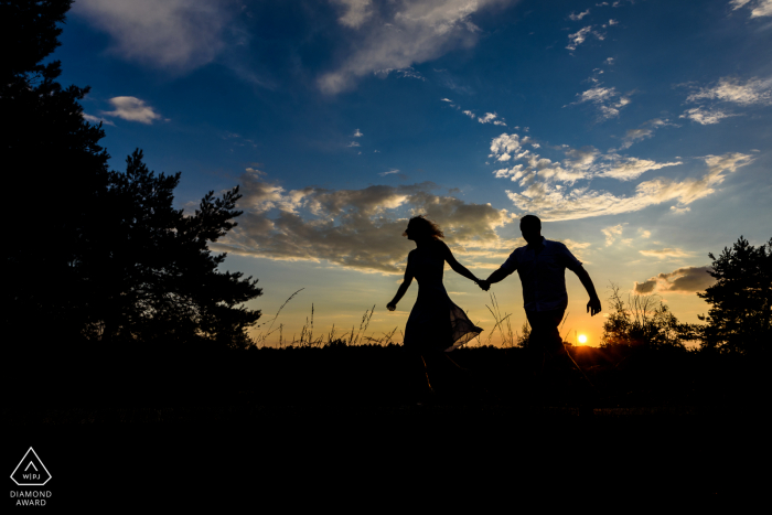 Heather près d'Eindhoven Silhouette image d'un couple en cours d'exécution au coucher du soleil.
