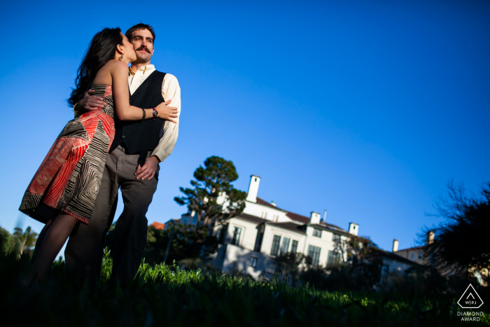 Blue CA sky engagement portrait of the couple in a gentle loving kiss in SF, CA