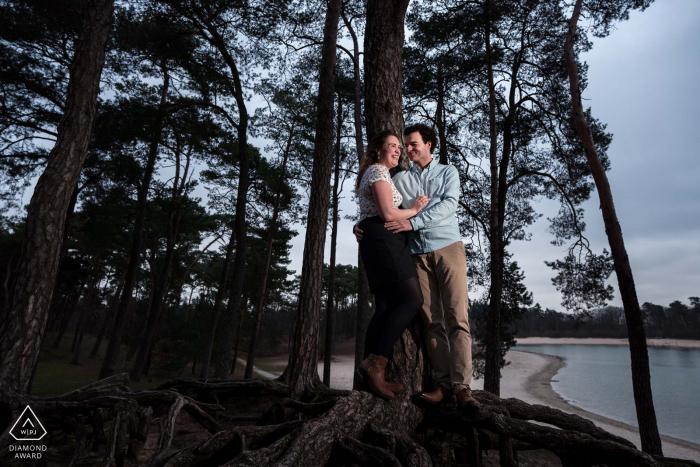Ce couple nouvellement fiancé est debout sur les racines d'un arbre avec une vue incroyable sur le Henschotemeer