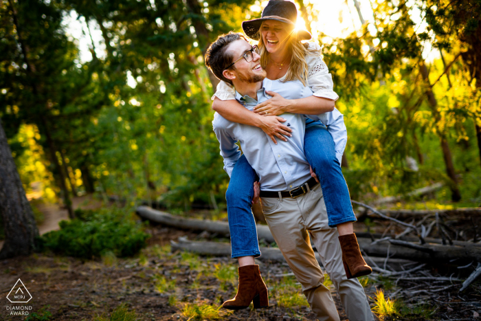 Future groom gives his future bride a piggy back ride during their engagement session at Meyer Ranch Park in Morrison, CO