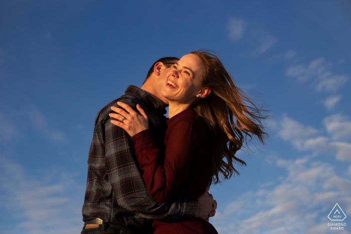 Alberta engagement photo shoot at Astonin Lakewith a Couple laughing with clear blue sky above