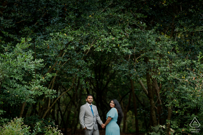 Houston Arboretum outside forest picture session before the wedding with a Couple under a lush tree awning