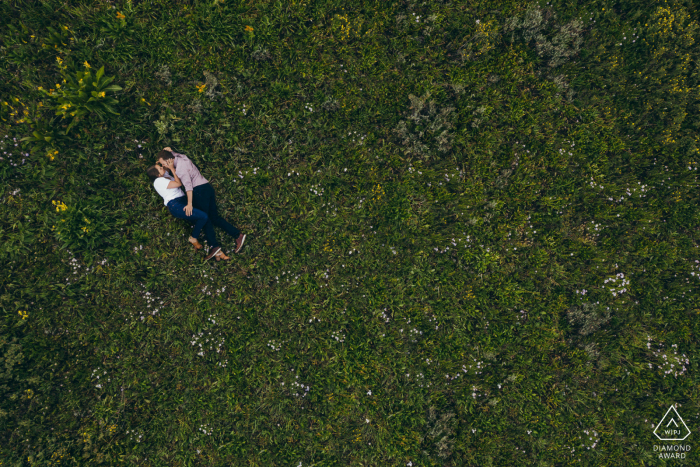 Crested Butte mini engagement photo session before the wedding day with the Couple laying in a field