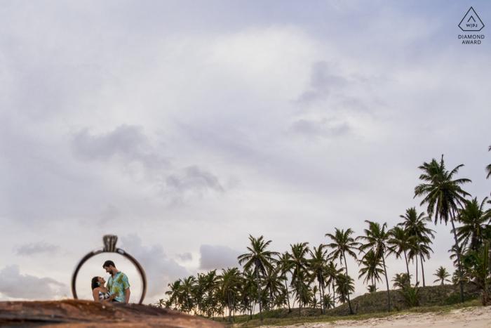 Marechal Deodoro mini séance de photographie de couple de plage avant le jour du mariage avec une image prise à travers la bague de fiançailles dans le sable