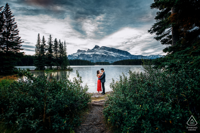 Two Jacks Lake, AB, Canada mini beach couple photography session before the wedding day while Holding each other outdoors in nature