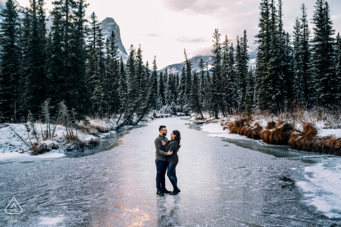 Canmore, AB, Canada outside winter picture session before the wedding day On the frozen creek