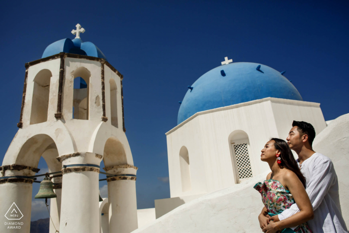 Santorini, Greece mini couple photo session before the wedding day against the white buildings with blue roofs and a blue sky