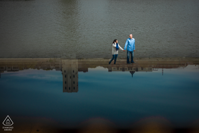 St Paul reflection portrait by the water in MN with a Couple walking near the water in the city