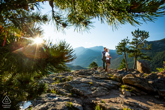 Estes Park, Colorado mountain couple photo shoot done as the sun sets behind the rocky mountains, the couple pose for an engagement portrait.