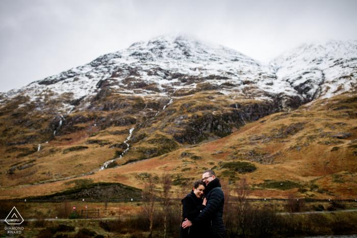 Glencoe Highlands couple fiancé séance photo avec quelques étreintes pour échapper au gel de l'Écosse