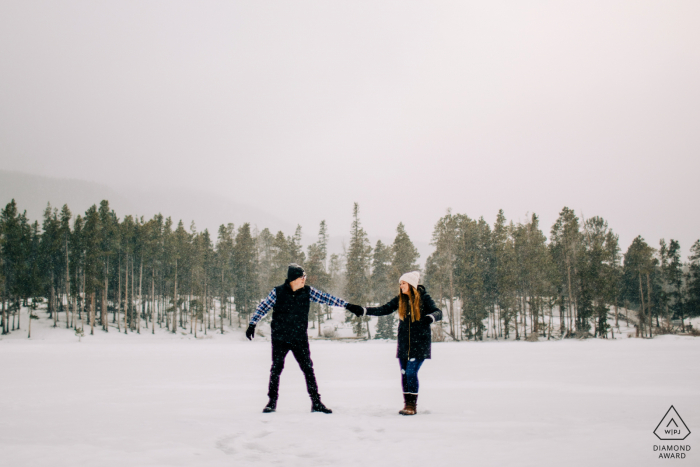 Colorado engaged winter picture session at Sprague Lake in RMNP with the Couple dancing on a frozen lake