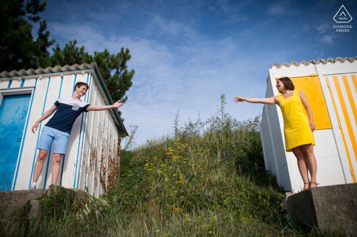 Séance photo de couple fiancé à Carnac avec des couleurs assorties de tenues, de vêtements et de peinture de construction