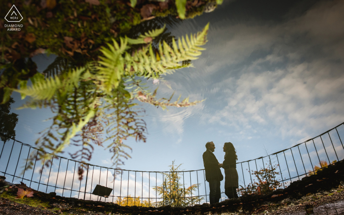 Mottisfont couple engagement pic session with some fence Reflections in the font at Mottisfont