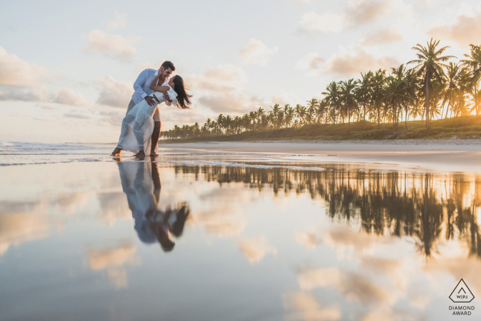 Marechal Deodoro couple pre-wed portrait in front of the sea with water reflections at sunset with some gentle wind