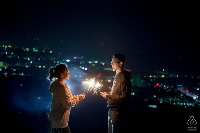 Nanning Fine Art Engagement Session at night overlooking the city lights with a couple holding sparklers