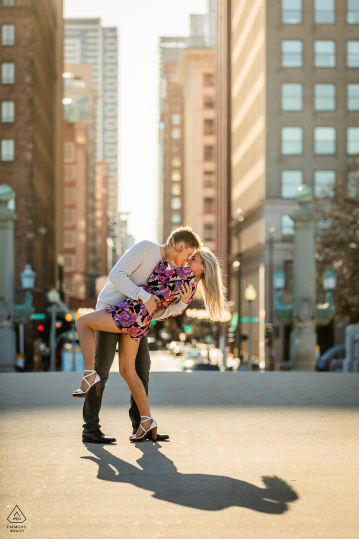 Downtown Chicago environmental engagement e-session while a Couple kisses in a dipping pose during golden hour