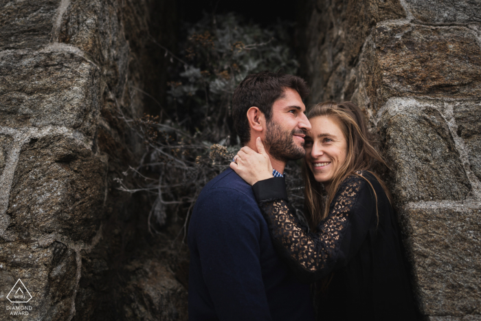 Saint Cast, France environmental engagement e-session with a couple in dark tones in a stone building cove