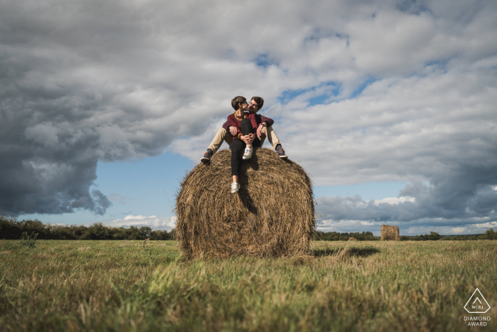 Gulf du Morbihan, France environmental engagement e-session with the young couple sitting on a large round hay bale in the open field