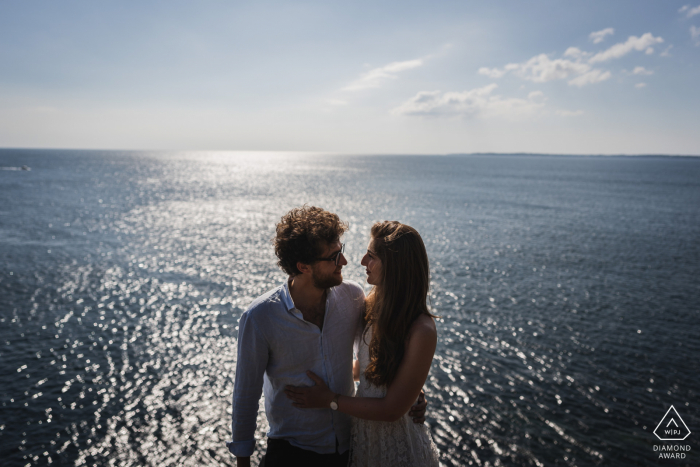 Crozon, France portrait e-session with The couple high above the water created while shooting toward the sun