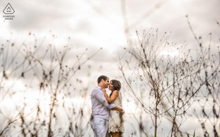 Maceió, e-session d'engagement environnemental d'Alagoas avec le couple s'embrassant dans une ferme et l'herbe sèche forme un cadre pour eux