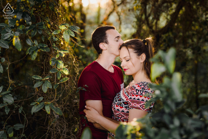 True Love Pre-Wedding Portrait Session in Montpellier capturing a couple kissing in the green lush forest