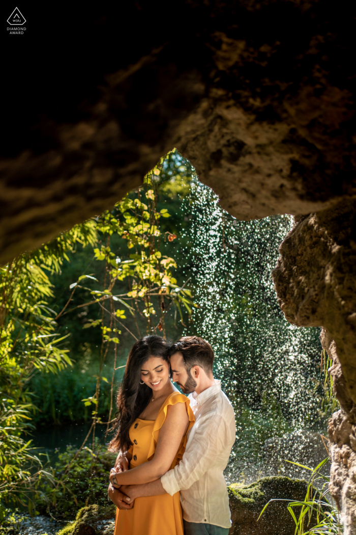 Neuilly sur Seine couple e-session at Parc de Bagatelle in the rock cave under the soft waterfall