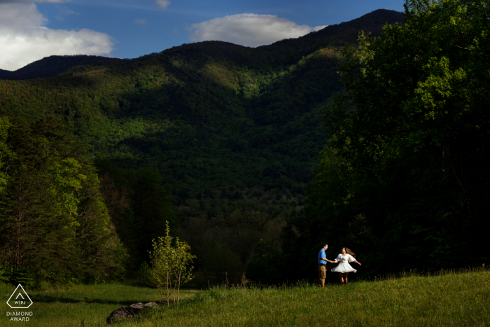 """Asheville bride and groom to be, modeling for a NC pre-wedding picture by North Carolina Photographer """"I used the shadows of the mountain, to give me a background to make the couple pop out. She started spinning and I captured her in a great moment"""""""