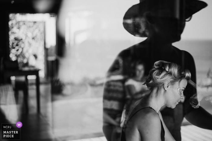 El fotógrafo de bodas de Bali capturó este reflejo en blanco y negro de una novia que se arreglaba el cabello mientras alguien mira por la ventana
