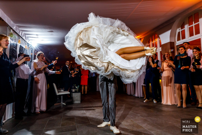 Overjissel wedding photographer captured this image of a bride in mid twirl with her feet off the ground as she and her groom have their first dance in front of wedding guests