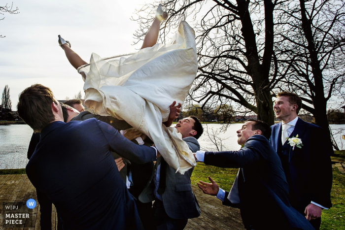 Netherlands wedding photographer created this silly image of a bride being tossed in the air by the groomsmen