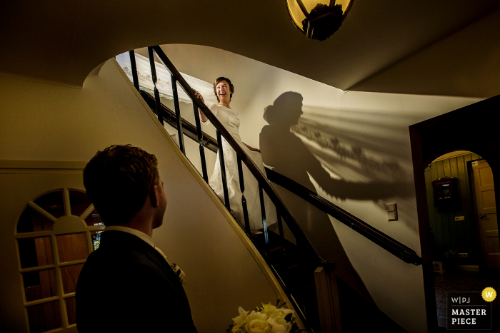 Netherlands wedding photographer captured this photo of a bride walking down a curved staircase as her groom waits at the bottom