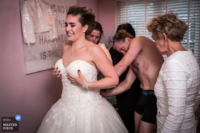 This image of the bride getting assistance putting on her dress was captured by a Noord Hollands wedding photographer
