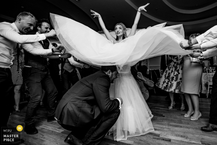 Dublin guests hold up part of the brides dress while the groom is underneath it