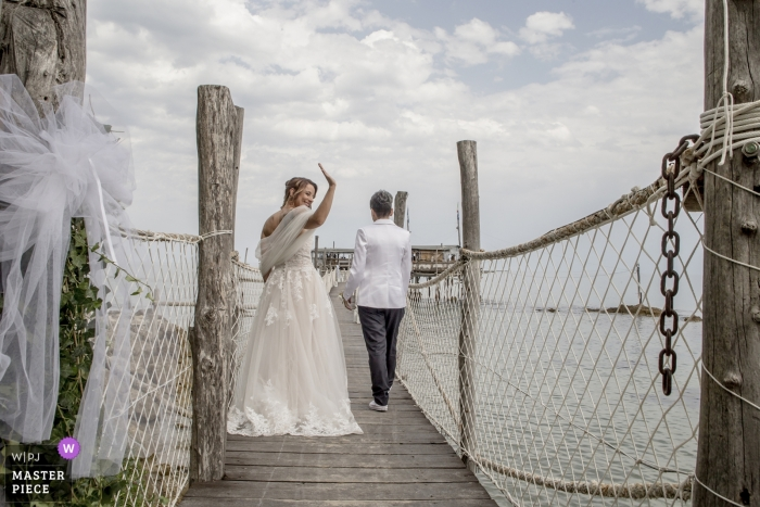 Abruzzo bride waves as she and the groom leave the wedding