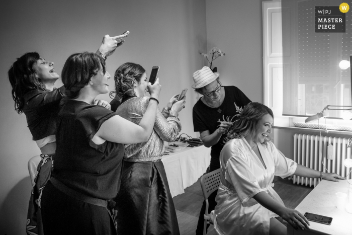 Marche bridesmaids taking photos of the bride as she gets her hair ready before the wedding