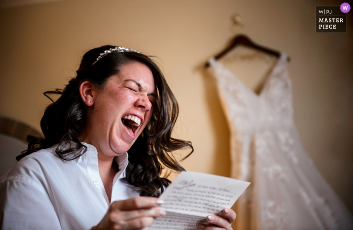 New Jersey bride reading a letter from her fiancé before the wedding with her dress in the background