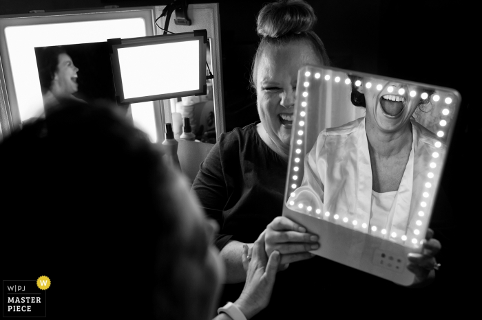 Yosemite, California bride smiles as she sees her make up in the mirror