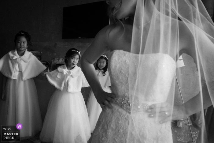 Floreros de Los Angelos mirando a la novia en su vestido antes de la boda
