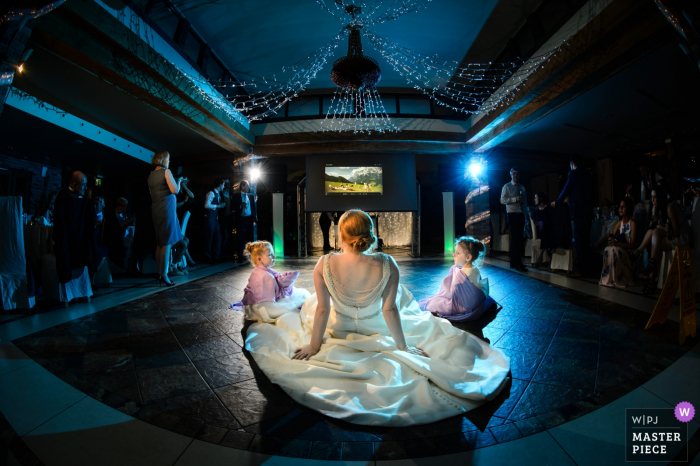 Guernsey bride sits with two girls on the dance floor at the reception