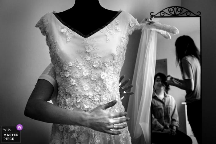 La novia de Londres, Reino Unido, prepara su cabello en el espejo con el vestido delante de ella
