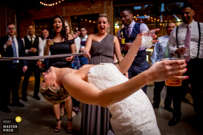 Chicago, Illinois bride holds her drinks and plays limbo at the same time at the wedding reception